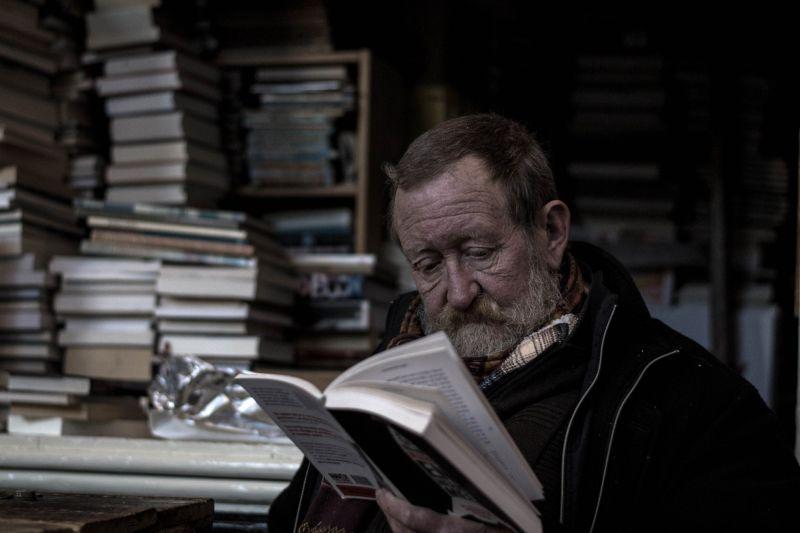 Zdjęcie starszego człowieka czytającego książkę